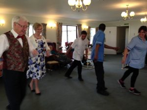 Staff have a dance with Mike and Muriel