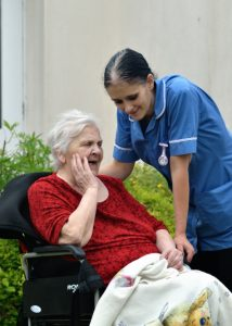Carer Amy laughs with resident Iris